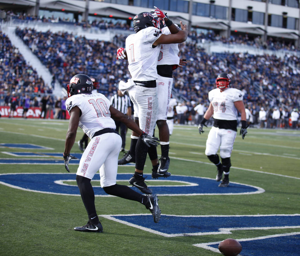 UNLV Rebels quarterback Armani Rogers (1) celebrates scoring a touchdown with UNLV Rebels running back Tyree Jackson (26) during the first half of their game against the Nevada Wolf Pack in Reno S ...