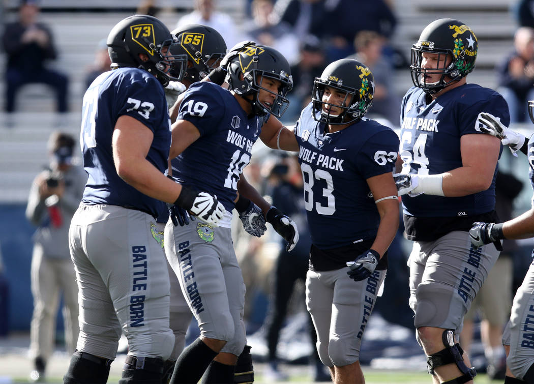 Nevada Wolf Pack wide receiver Wyatt Demps (19) celebrates scoring a touchdown with  wide receiver Andrew Celis (83), offensive lineman Sean Krepsz (64), offensive lineman Clifford Porter (65) and ...