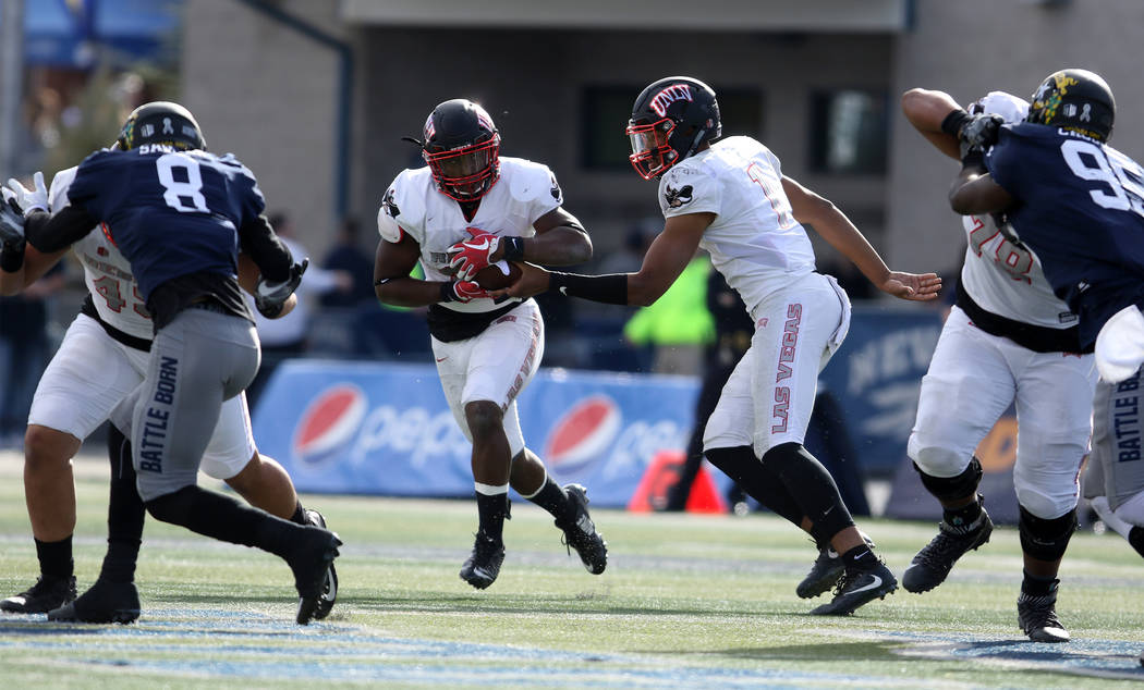 UNLV Rebels quarterback Armani Rogers (1) hands off the football to running back Lexington Thomas (3) during the first half of their game against the Nevada Wolf Pack in Reno, Saturday, Nov. 25, 2 ...