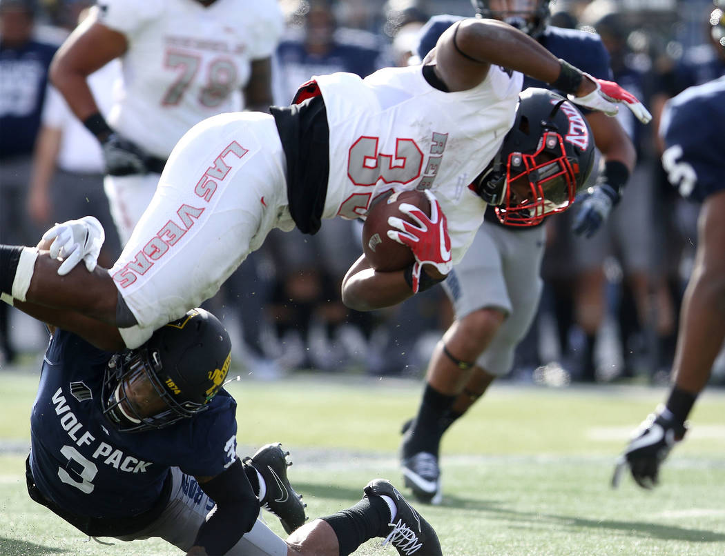 UNLV Rebels running back Xzaviar Campbell (35) runs with the football and is tackled by Nevada Wolf Pack defensive back Ahki Muhammad (3) during the first half of their game in Reno, Saturday, Nov ...