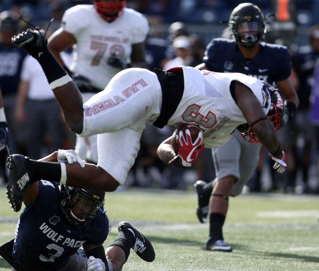 UNLV Rebels defensive back Dalton Baker (33) returns the football and is tackled by Nevada Wolf Pack defensive back Ahki Muhammad (3) during the first half of their game in Reno Saturday, Nov. 25, ...