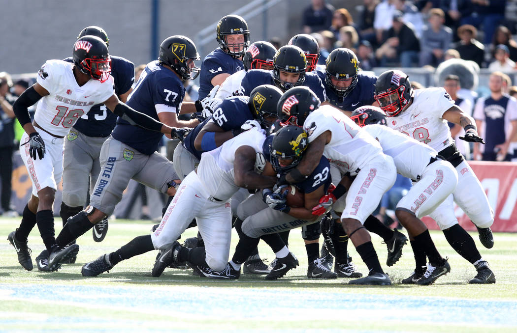 Nevada Wolf Pack running back Kelton Moore (23) fights for yards as is tackled by multiple UNLV Rebels defenders during the first half of their game in Reno, Saturday, Nov. 25, 2017. Heidi Fang La ...