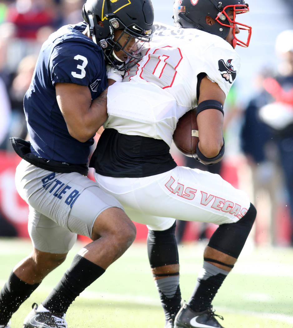 UNLV Rebels wide receiver Brandon Presley (80) catches the football and is tackled by Nevada Wolf Pack defensive back Ahki Muhammad (3) during the first half of their game in Reno Saturday, Nov. 2 ...