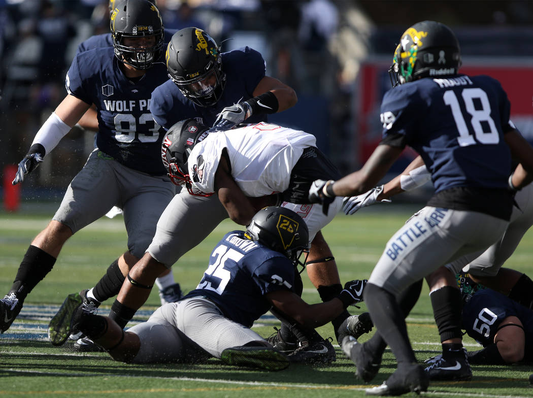 UNLV Rebels running back Lexington Thomas (3) gets tackled by Nevada Wolf Pack defensive back Daniel Brown (25) as other defenders swarm in during the first half of their game in Reno, Saturday, N ...