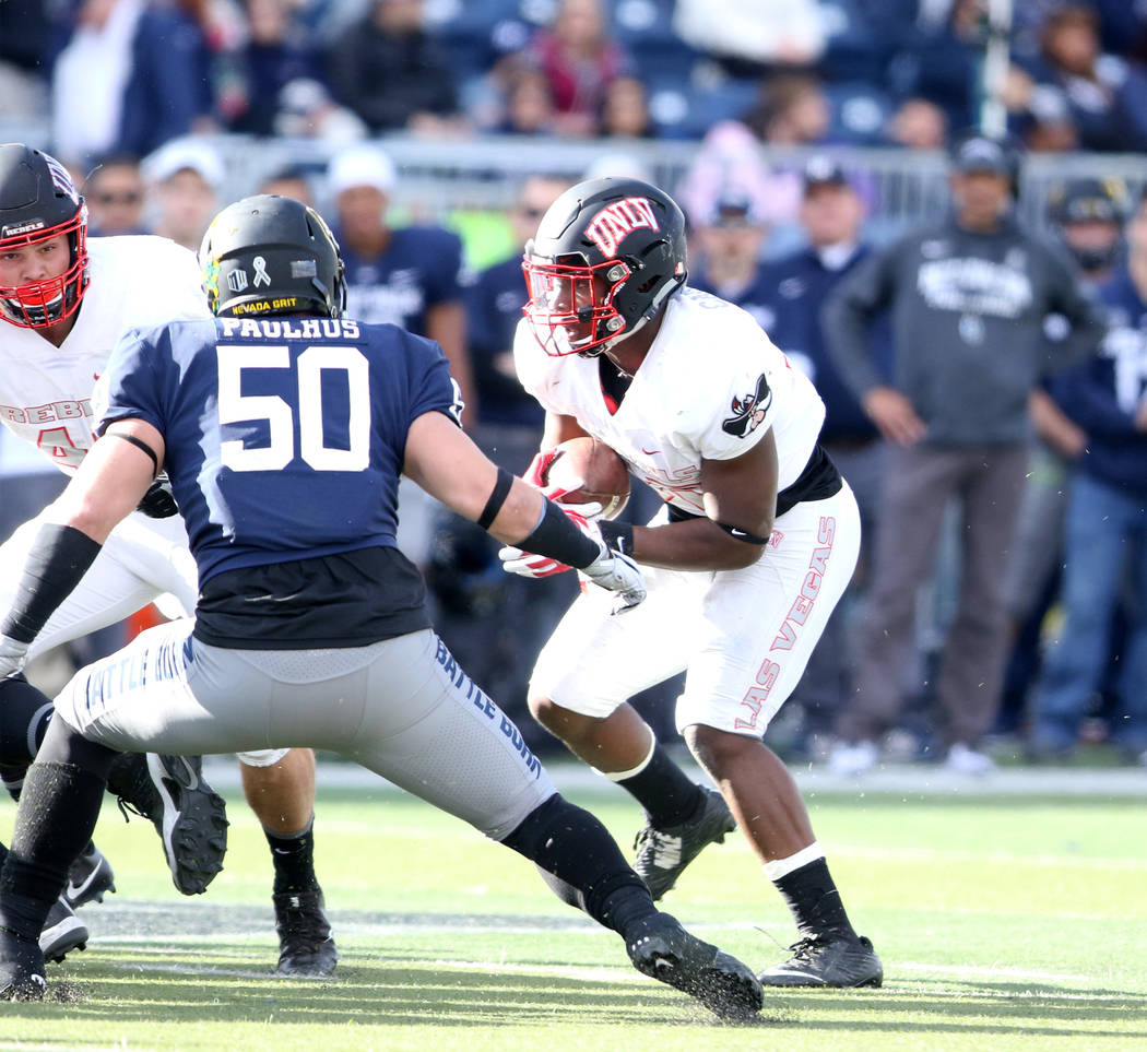 UNLV Rebels running back Xzaviar Campbell (35) tries to run downfield as Nevada Wolf Pack linebacker Austin Paulhus (50) prepares to tackle him during the first half of their game in Reno, Saturda ...