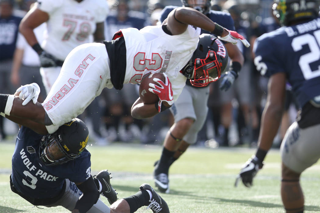 UNLV Rebels defensive back Dalton Baker (33) returns the football and is tackled by Nevada Wolf Pack defensive back Ahki Muhammad (3) during the first half of their game in Reno, Nevada, Saturday, ...
