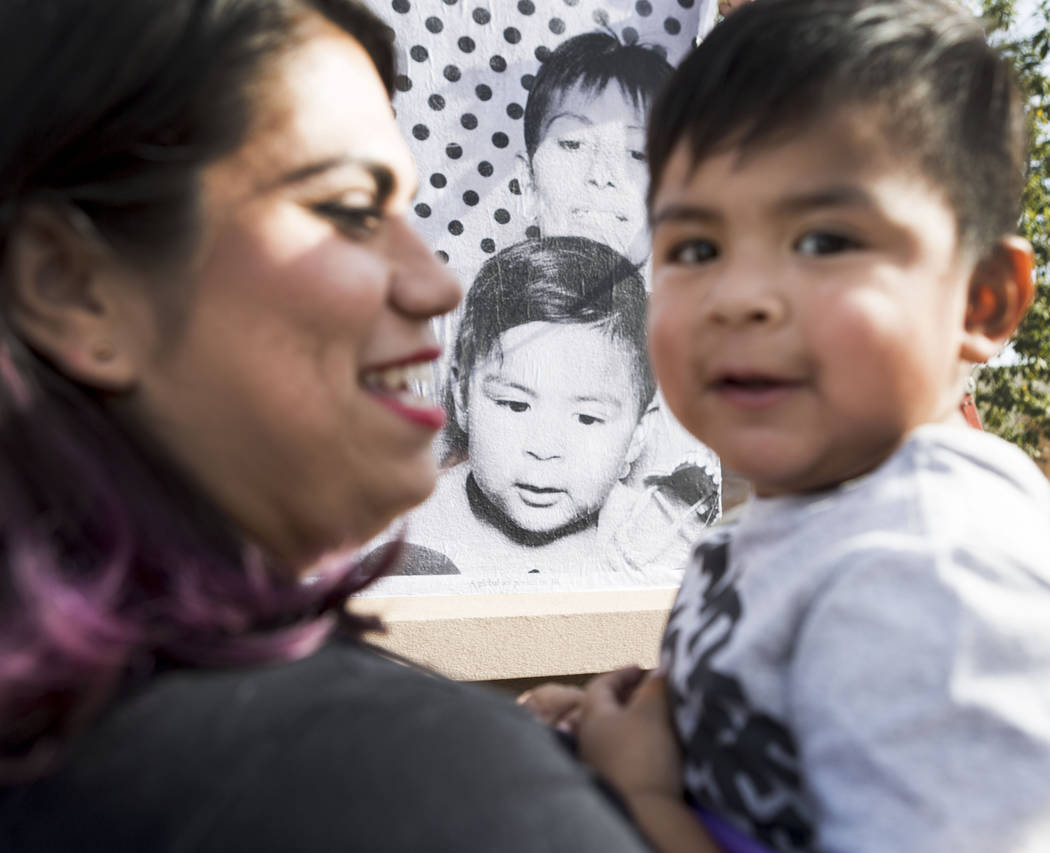 Astrid Silva, left, holds her nephew Noah, 2, in front of a large scale print portrait of himself taken from the Inside Out Project truck that stopped at the East Las Vegas Community Center in Las ...