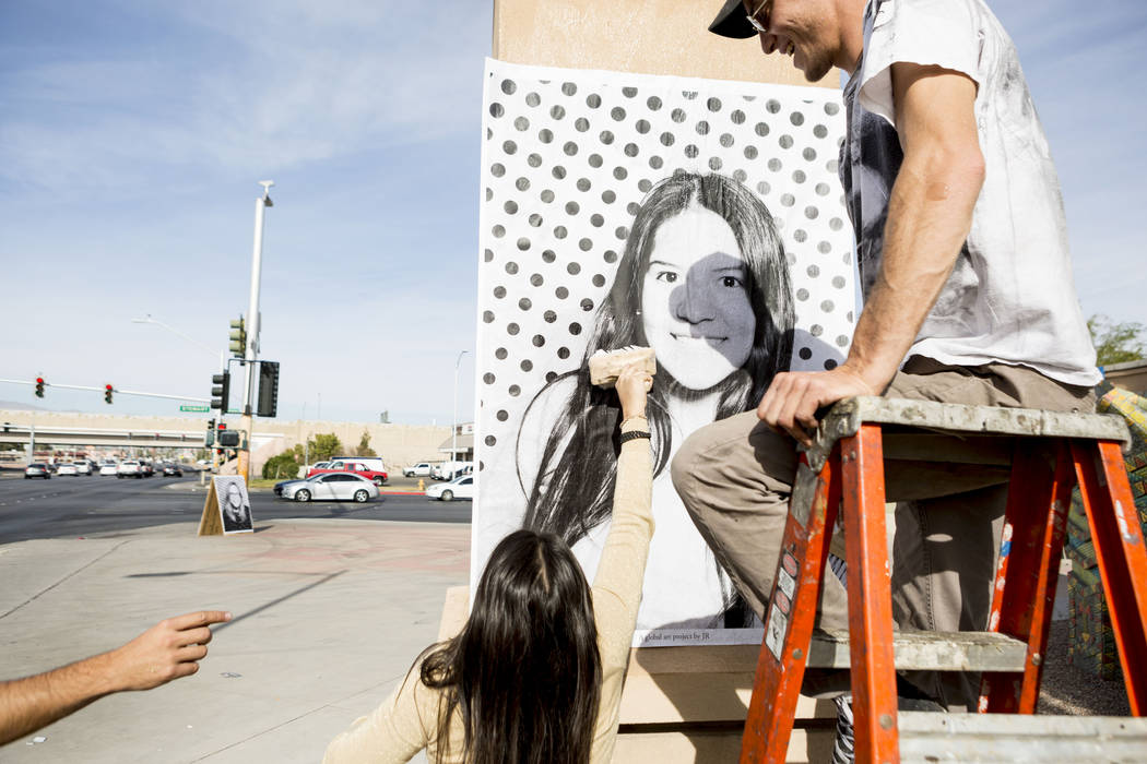 Angela Rebaza, left, originally from Peru now residing in Las Vegas, helps Alexander Pierre with the Inside Out Project paste her large scale print of herself to celebrate  DACA recipients at the  ...