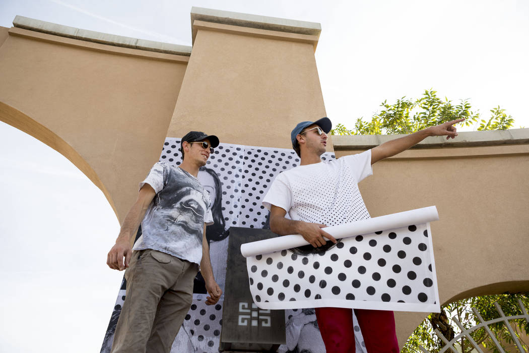 Alexander Pierre, left, and Marz Holden-Montini, with the Inside Out Project for Dreamers paste large prints of DACA recipients at the East Las Vegas Community Center in Las Vegas, Monday, Nov. 13 ...