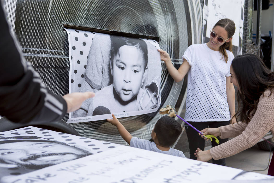 Noah, 2, center, reaches for a large scale print of himself from the Inside Out Project truck that stopped at the East Las Vegas Community Center in Las Vegas to celebrate DACA recipients Monday,  ...