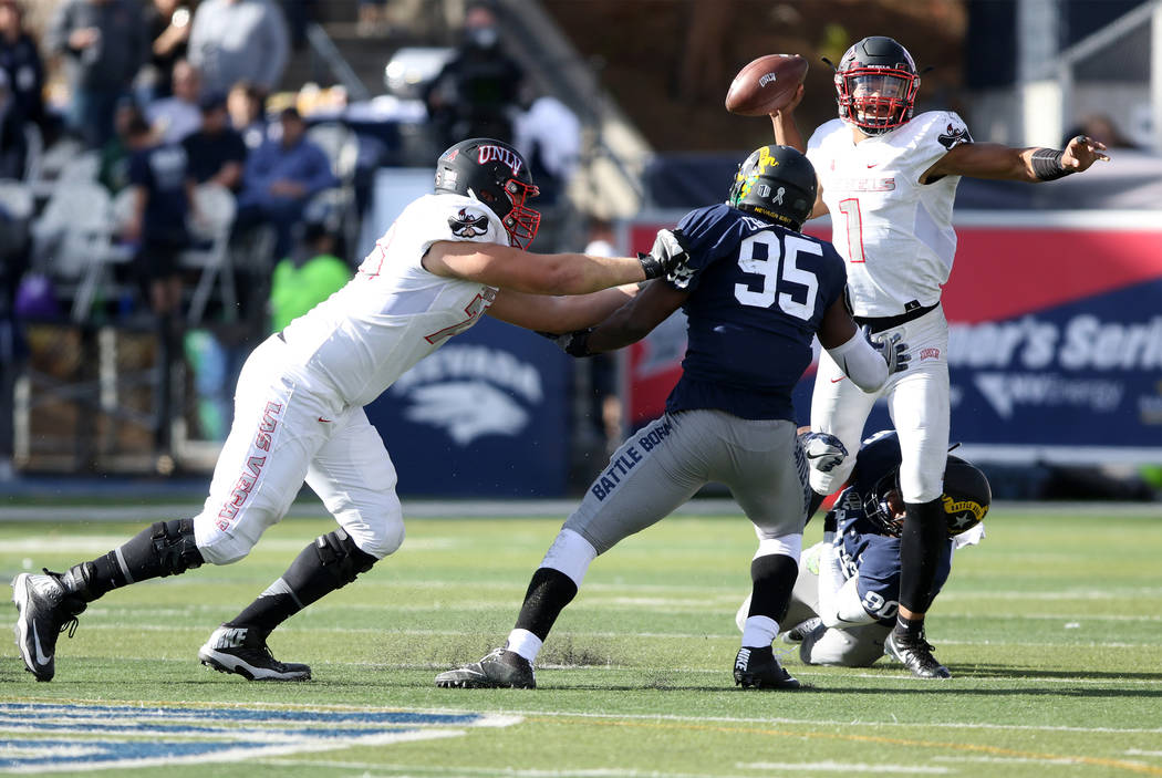 UNLV Rebels quarterback Armani Rogers (1) throws the football before being tackled by Nevada Wolf Pack defensive end Malik Reed (90) during the first half of their game in Reno, Saturday, Nov. 25, ...