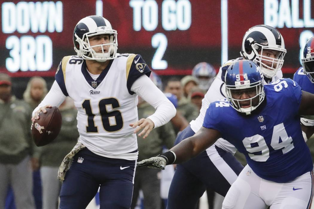 Los Angeles Rams' Jared Goff (16) looks to pass during the first half of an NFL football game as New York Giants' Dalvin Tomlinson (94) closes in Sunday, Nov. 5, 2017, in East Rutherford, N.J. Gof ...