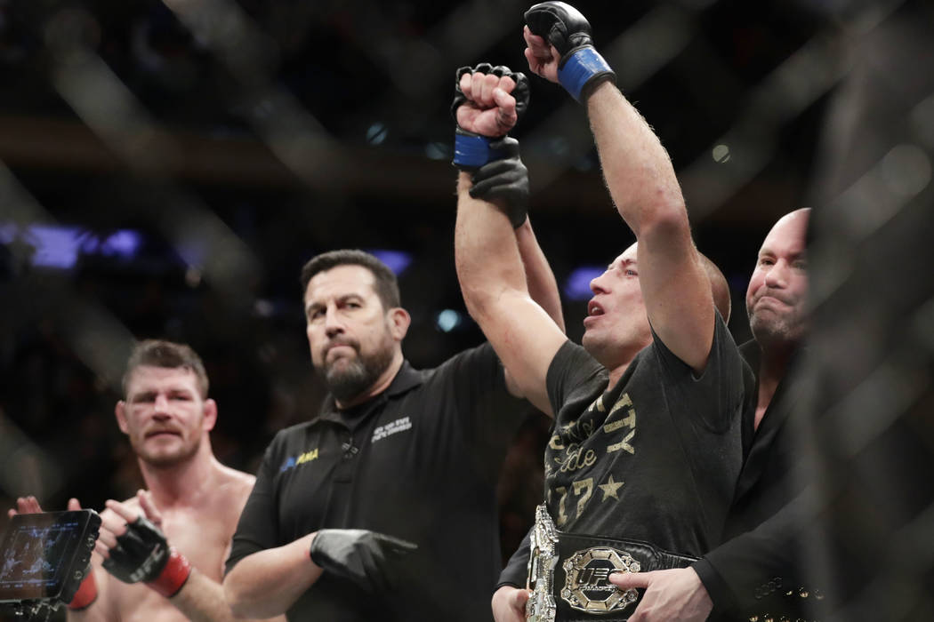 Georges St-Pierre, right, of Canada, celebrates after defeating England's Michael Bisping, left, in a middleweight title mixed martial arts bout at UFC 217 early Sunday, Nov. 5, 2017, in New York. ...
