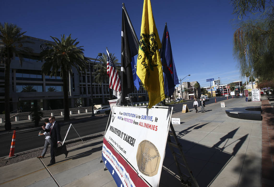People walk past signs placed in support of the Bundy family and others outside the in Lloyd George U.S. Courthouse in downtown Las Vegas on Tuesday, Nov. 14, 2017. Opening statements were deliver ...