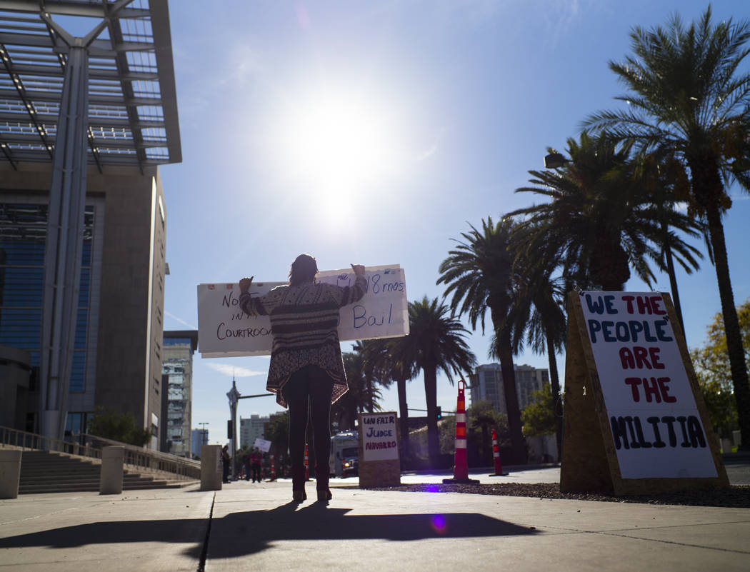 Julie Setzer holds signs in support of the Bundy family and others outside the in Lloyd George U.S. Courthouse in downtown Las Vegas on Tuesday, Nov. 14, 2017. Opening statements were delivered in ...
