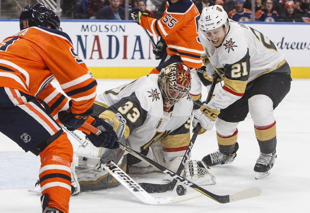 Vegas Golden Knights goalie Maxime Lagace (33) makes the stop on Edmonton Oilers' Drake Caggiula (91) as Golden Knights' Cody Eakin (21) tries for the rebound during the second period of an NHL ho ...
