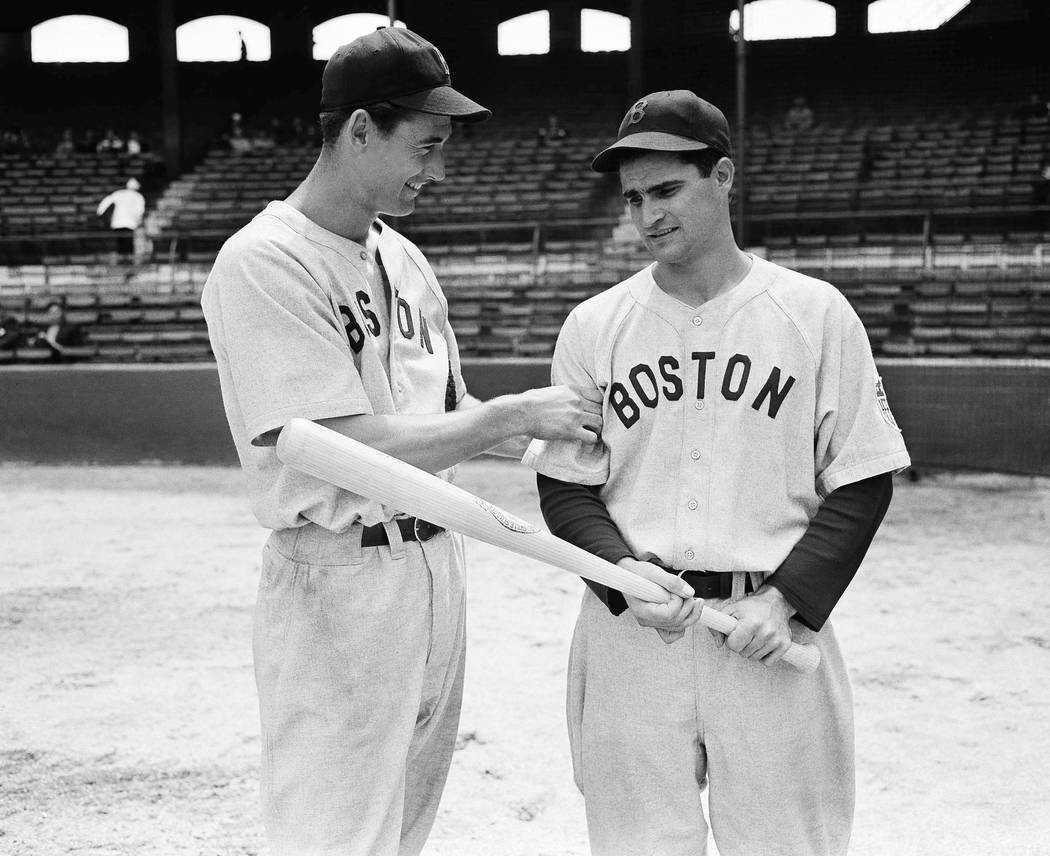 In this May 14, 1942, file photo, Boston Red Sox left fielder Ted Williams, left, tests the arm of Red Sox second baseman Bobby Doerr before their game against the White Sox, in Chicago. Doerr, a  ...
