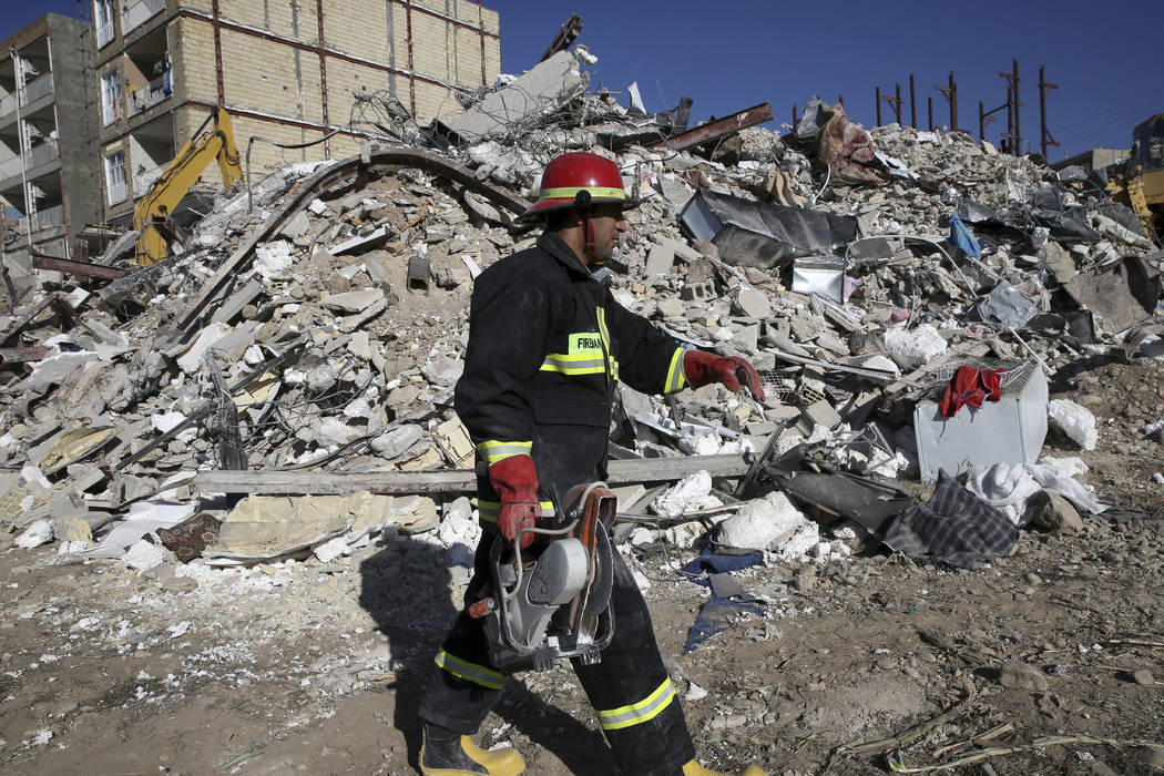 A rescue worker walks past the rubble of a collapsed building at an earthquake site in Sarpol-e-Zahab in western Iran, Tuesday, Nov. 14, 2017. Rescuers are digging through the debris of buildings  ...