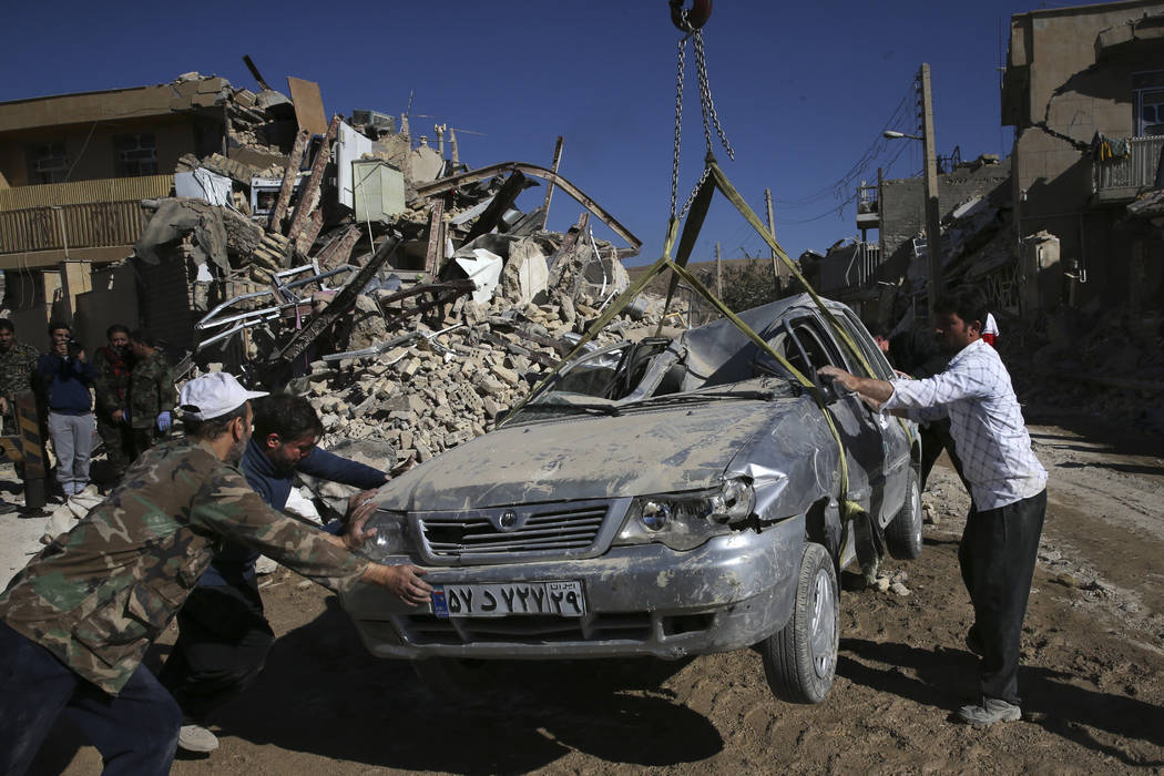 People and rescuers move a destroyed car on the earthquake site in Sarpol-e-Zahab in western Iran, Tuesday, Nov. 14, 2017. Rescuers are digging through the debris of buildings felled by the Sunday ...