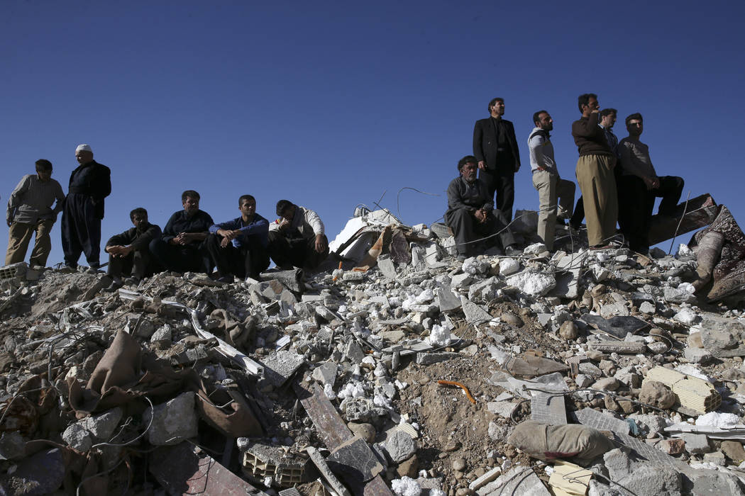 Survivors sit on the debris while rescuers search on the earthquake site in Sarpol-e-Zahab in western Iran, Tuesday, Nov. 14, 2017. Rescuers on Tuesday used backhoes and heavy equipment to dig thr ...