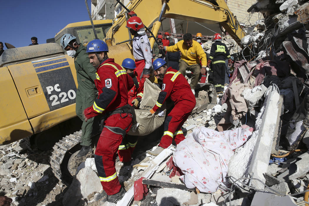 Rescuers carry away the body of an earthquake victim in Sarpol-e-Zahab in western Iran, Tuesday, Nov. 14, 2017. Rescuers are digging through the debris of buildings felled by the Sunday earthquake ...