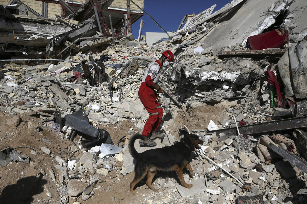 A rescue worker searches the debris with his sniffing dog on the earthquake site in Sarpol-e-Zahab in western Iran, Tuesday, Nov. 14, 2017. Rescuers are digging through the debris of buildings fel ...