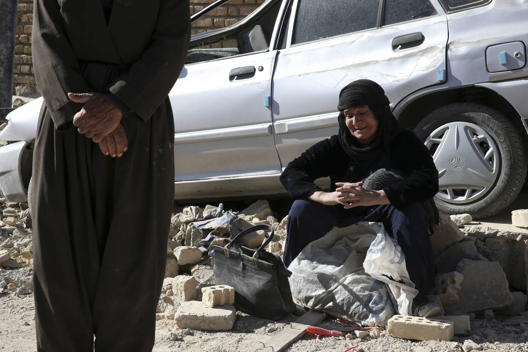 A woman sits on the debris on the earthquake site in Sarpol-e-Zahab in western Iran, Tuesday, Nov. 14, 2017. Rescuers are digging through the debris of buildings felled by the Sunday earthquake in ...