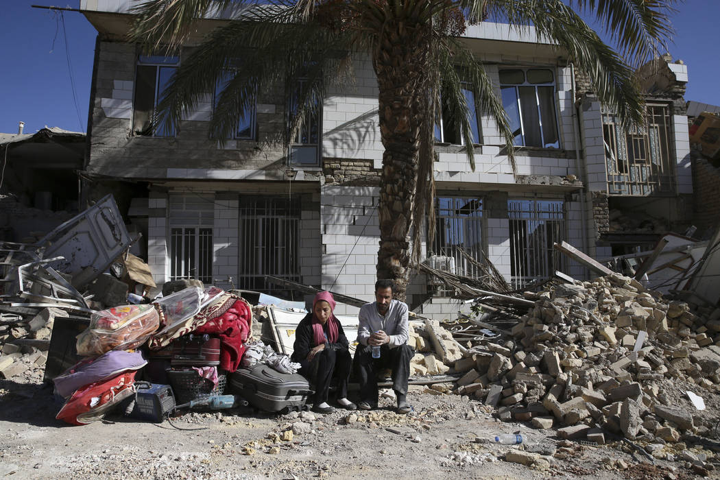 Survivors sit in front of a destroyed house on the earthquake site in Sarpol-e-Zahab in western Iran, Tuesday, Nov. 14, 2017. Rescuers are digging through the debris of buildings felled by the Sun ...