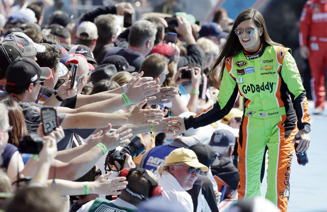 FILE - In this Feb. 22, 2015, file photo, driver Danica Patrick greets fans as she is introduced before the start of the Daytona 500 NASCAR Sprint Cup series auto race at Daytona International Spe ...