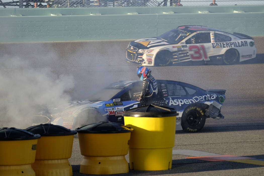 Danica Patrick climbs out of her car as it catches fire after hitting the wall on turn two during the NASCAR Cup Series auto race at Homestead-Miami Speedway in Homestead, Fla., Sunday, Nov. 19, 2 ...
