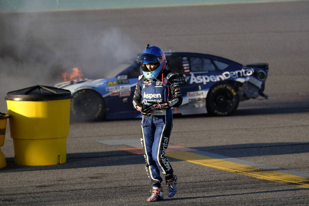 Danica Patrick walks away from her car as it catches fire after hitting the wall on turn two during the NASCAR Cup Series auto race at Homestead-Miami Speedway in Homestead, Fla., Sunday, Nov. 19, ...
