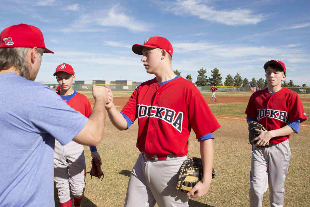 Players from the traveling youth baseball team Russian Wolves from Moscow receive a fist bump from their coach Sasha Volkov, left, as they come off the filed between innings during a game at Coron ...