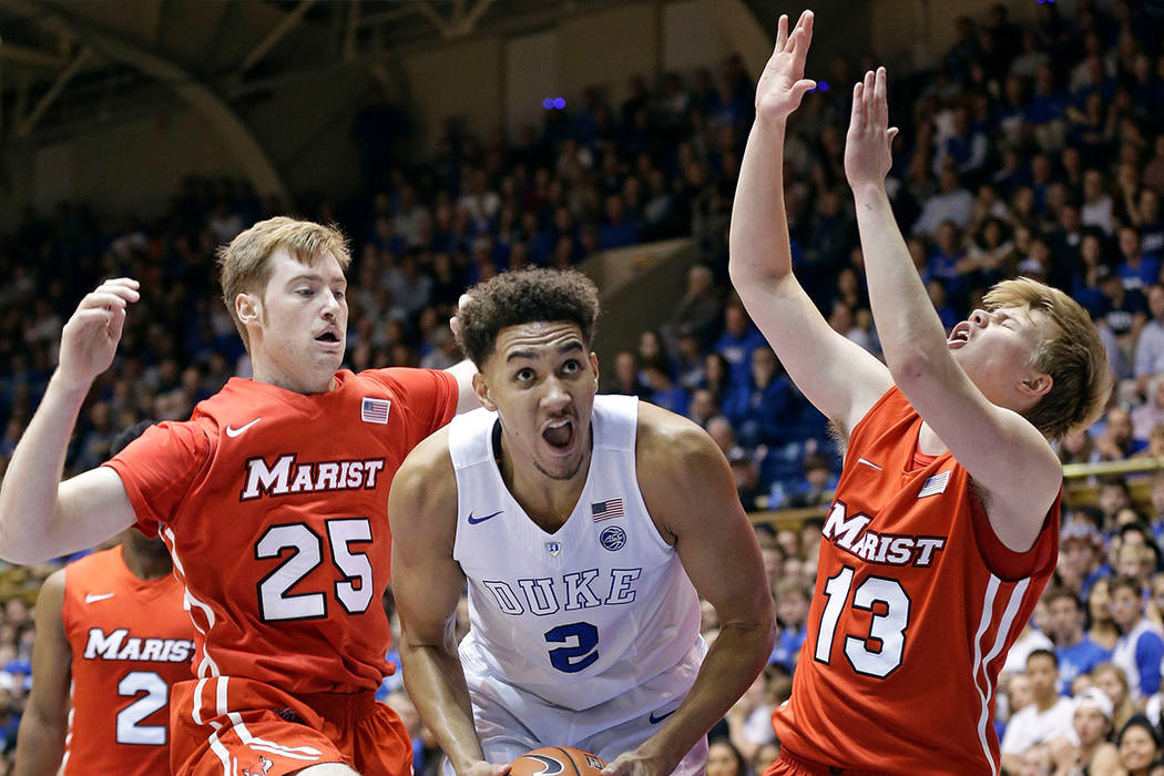 Duke forward Chase Jeter (2) drives between Marist center Connor McClenaghan (25) and Marist guard Kristinn Palsson (13) during the first half of an NCAA college basketball game. (AP Photo/Gerry B ...
