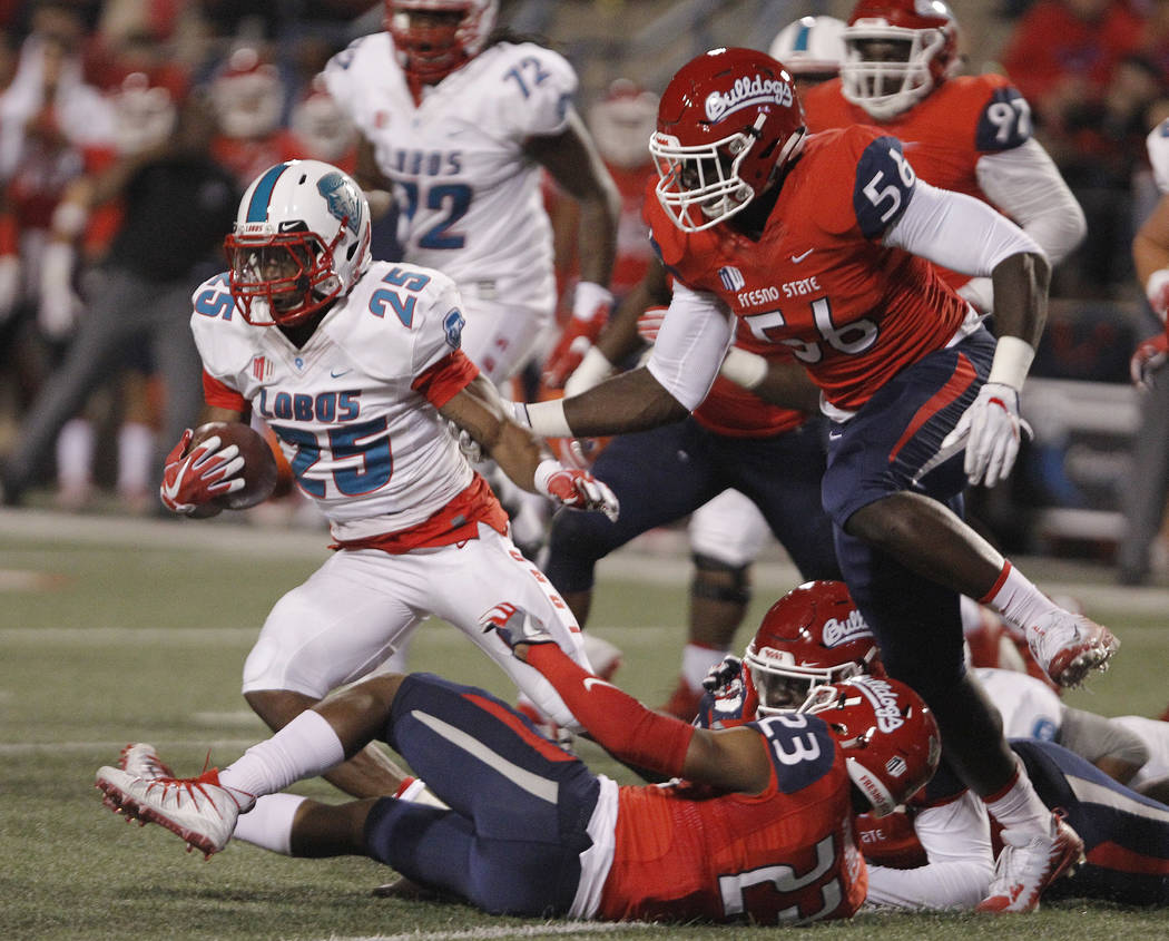 New Mexico's Tyrone Owens is chased by Fresno State's Tobenna Okeke, right, during the first half of an NCAA college football game in Fresno, Calif., Saturday, Oct. 14, 2017. (AP Photo/Gary Kazanjian)