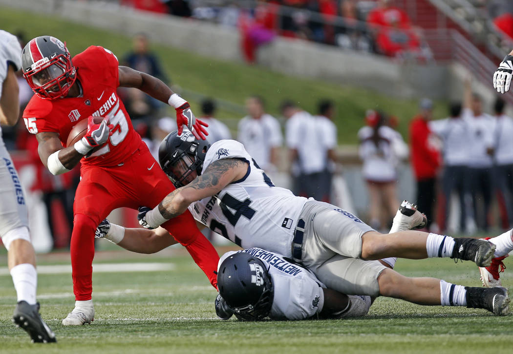 New Mexico running back Tyrone Owens (25) is stopped by Utah State linebacker Dalton Baker (24) and linebacker Kevin Meitzenheimer during the first half of an NCAA college football game in Albuque ...