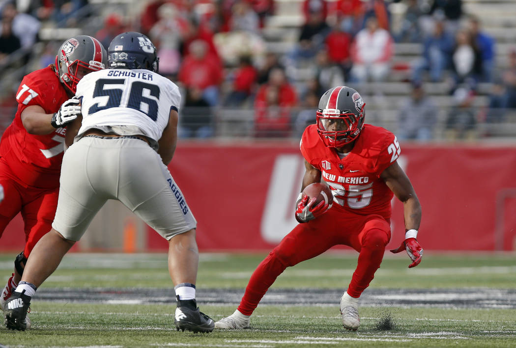 New Mexico running back Tyrone Owens (25) tries to elude Utah State nose guard Gasetoto Schuster (56) during the first half of an NCAA college football game in Albuquerque, N.M., Saturday, Nov. 4, ...