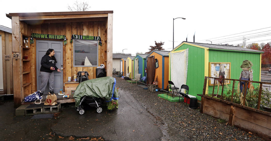 In this photo taken Thursday, Nov. 9, 2017, Eva Stough opens the door to her tiny house, where she lives with her partner and baby, at a homeless encampment in Seattle. Tiny homes could be the sol ...