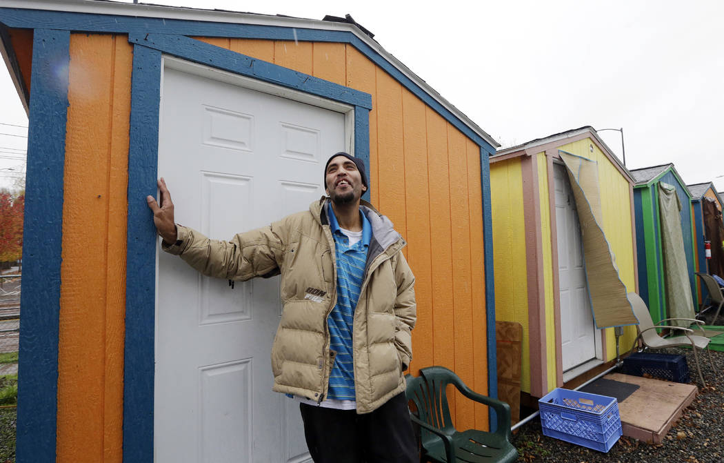 In this photo taken Thursday, Nov. 9, 2017, Tyson King stands at the door of his tiny house, where he has lived for nearly seven weeks, at a homeless encampment in Seattle. Tiny homes could be the ...