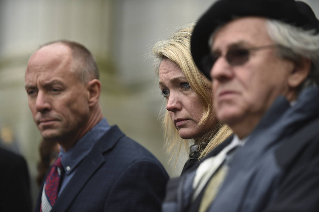 From left, Mark Barden, Nicole Hockley and Gil Rousseau listen during a press conference on the steps of the state Supreme Court after attending a hearing in a lawsuit against Remington Arms in Ha ...