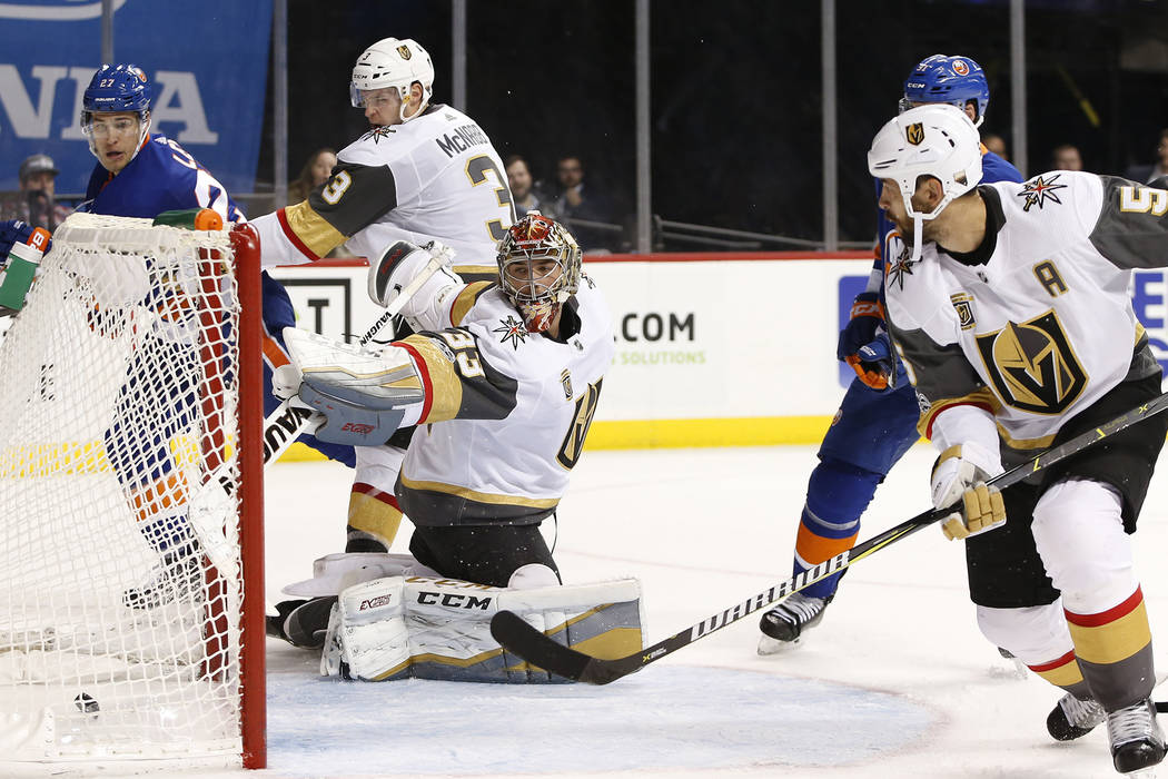 Vegas Golden Knights and Derek Engelland (5) watches as Vegas Knights goalie Maxime Lagace (33) watches Mathew Barzal's goal roll into the crease during the second period of an NHL hockey game aga ...