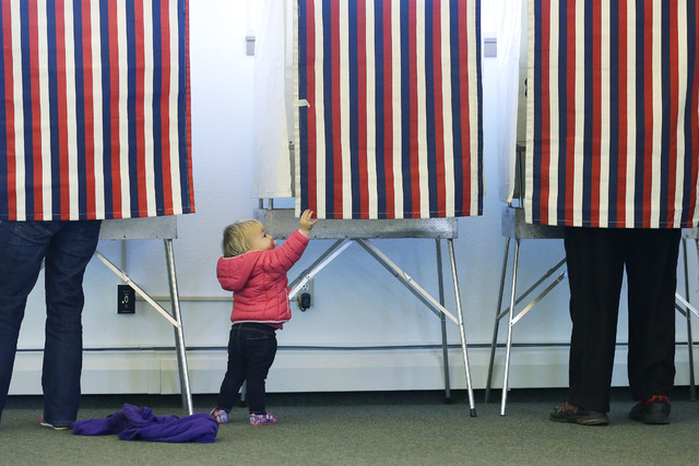 Zoe Buck, a 14-month-old child, checks out an empty voting booth as at her mother, Julie Buck, votes at left, Tuesday Nov. 4, 2014, at the Alaska Zoo polling place in Anchorage, Alaska. (Ted S. Wa ...