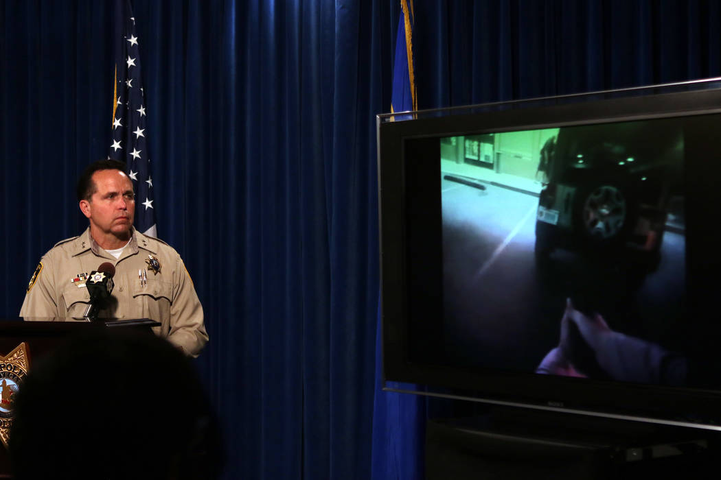 Las Vegas Metropolitan Police Department Assistant Sheriff Tom Roberts watches footage from a body camera of a shooting involving officer David Nesheiwat, not pictured, during a news briefing, Tue ...