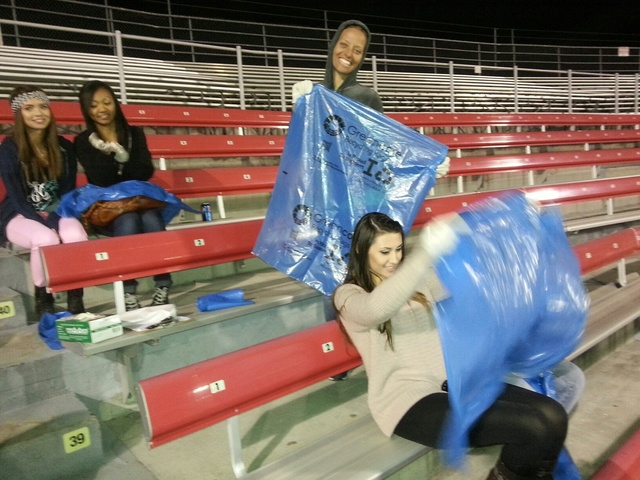 UNLV's recycling manager and sustainability coordinator Tara Pike-Nordstrom, center, smiles for the camera while picking up trash at Sam Boyd Stadium during the Game Day Recycling Challenge, a n ...