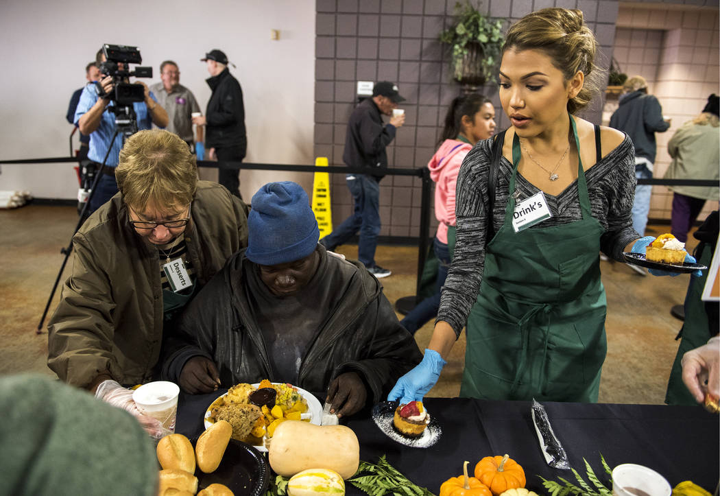 Volunteers Mickie Bonacci, left, and Geovanna Hilton, right, serve a patron her meal during Catholic Charities' annual Thanksgiving meal where about 175 volunteers help feed about 1,500 people fro ...