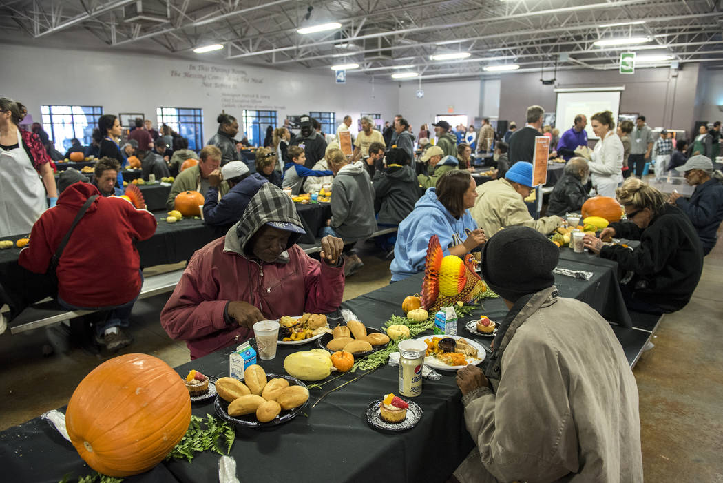 Patrons enjoy a free meal during Catholic Charities' annual Thanksgiving meal where about 175 volunteers help feed about 1,500 people from the Catholic Charities complex in Las Vegas on Thursday,  ...