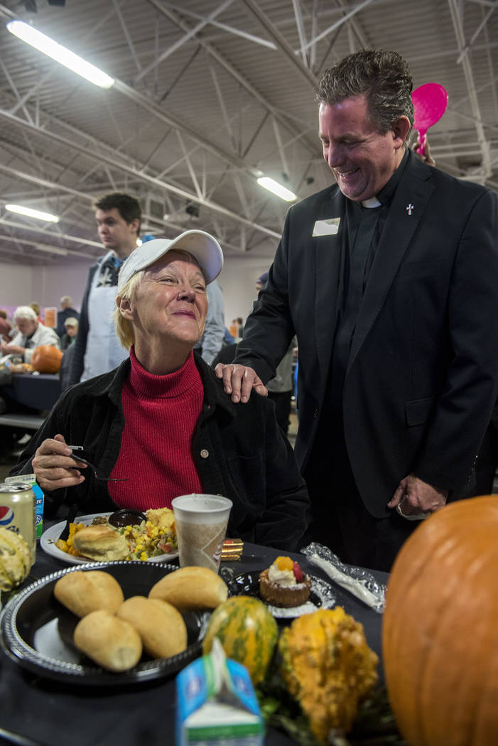 Deacon Thomas Roberts, right, visits with Mattie Barry during Catholic Charities' annual Thanksgiving meal where about 175 volunteers help feed about 1,500 people from the Catholic Charities compl ...
