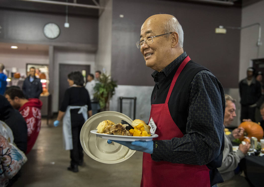 Owner of Lee's Liquor, Hae Un Lee volunteers during Catholic Charities' annual Thanksgiving meal where about 175 volunteers help feed about 1,500 people from the Catholic Charities complex in Las  ...