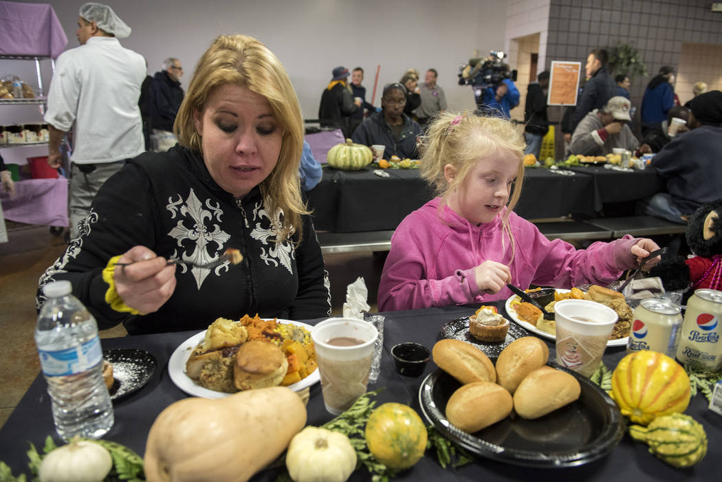 Mother Patricia Holm, left, and daughter Phoenix Holm, 7, eat their meal during Catholic Charities' annual Thanksgiving meal where about 175 volunteers help feed about 1,500 people from the Cathol ...