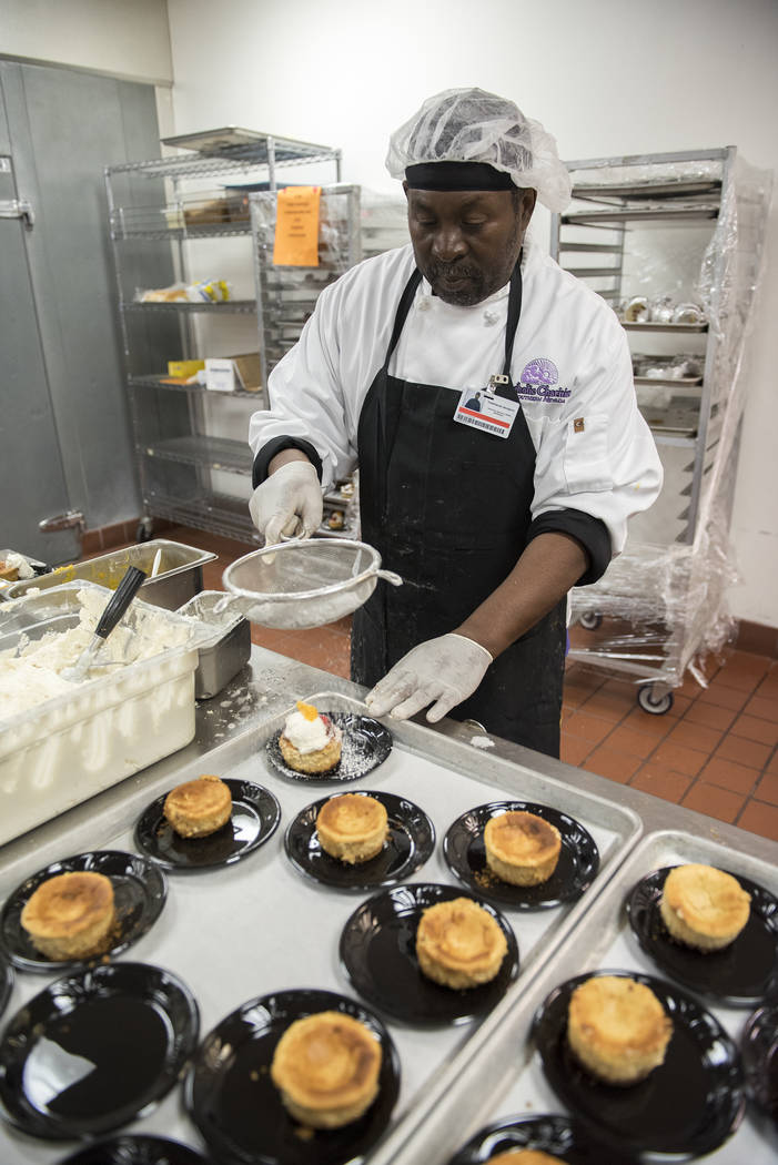 Volunteer Sim Ju prepares pumpkin cheesecake during Catholic Charities' annual Thanksgiving meal where about 175 volunteers help feed about 1,500 people from the Catholic Charities complex in Las  ...