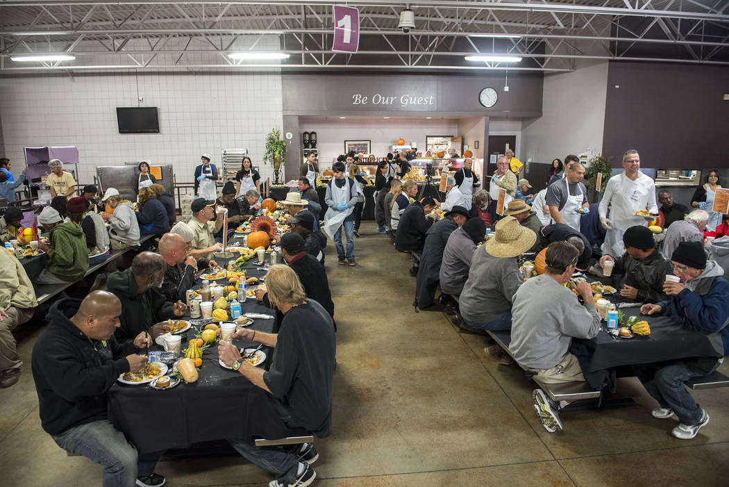 Patrons enjoy their meal during Catholic Charities' annual Thanksgiving meal where about 175 volunteers help feed about 1,500 people from the Catholic Charities complex in Las Vegas on Thursday, N ...